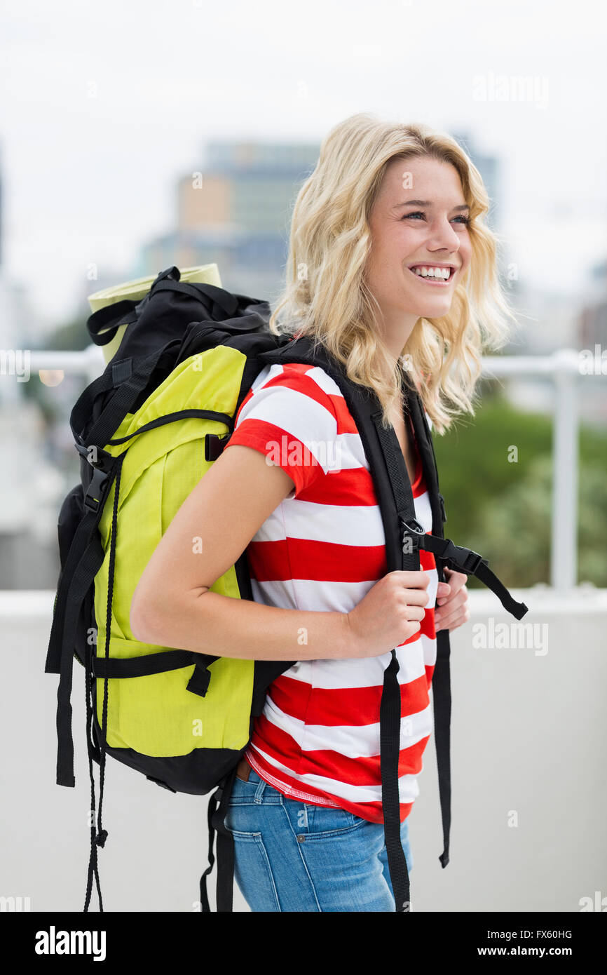 Young woman carrying backpack - Stock Image