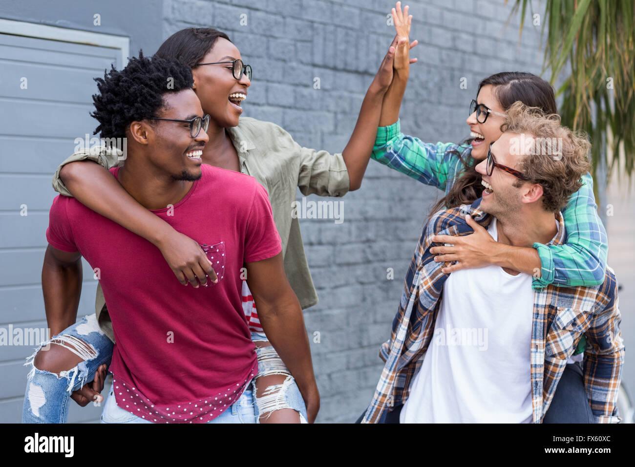 Young men giving piggyback to women - Stock Image
