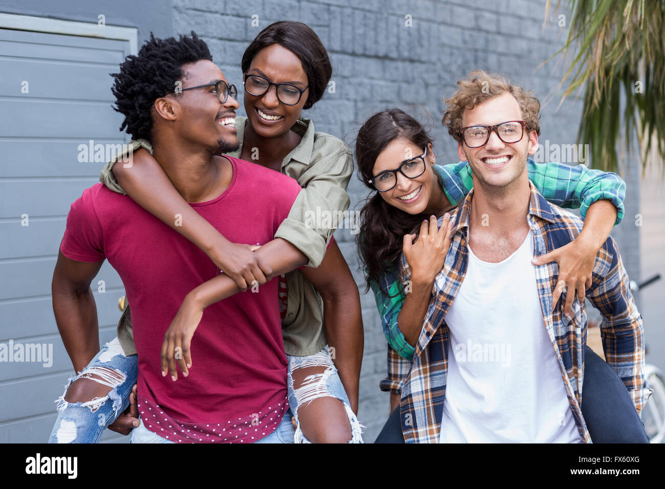 Young men giving piggyback to women - Stock Image