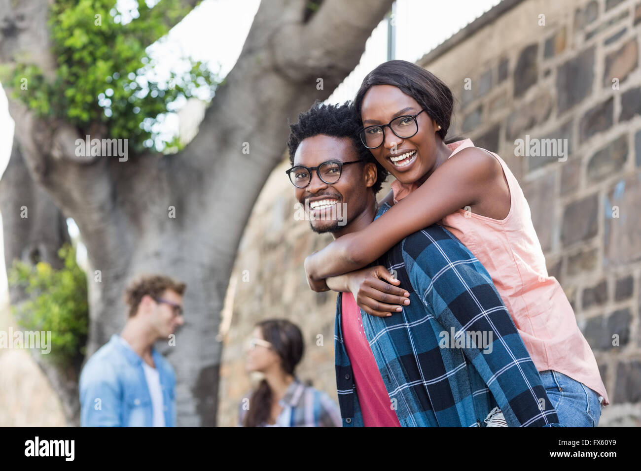 Young man giving piggyback to woman - Stock Image
