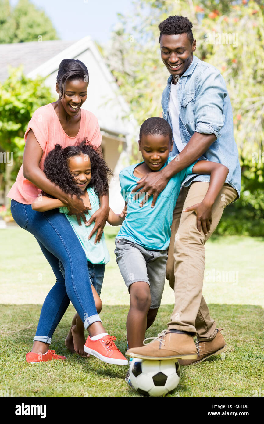 Happy family playing football - Stock Image