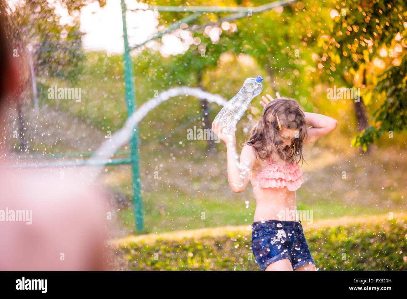 Unrecognizable boy splashing girl with water gun, sunny summer - Stock Image