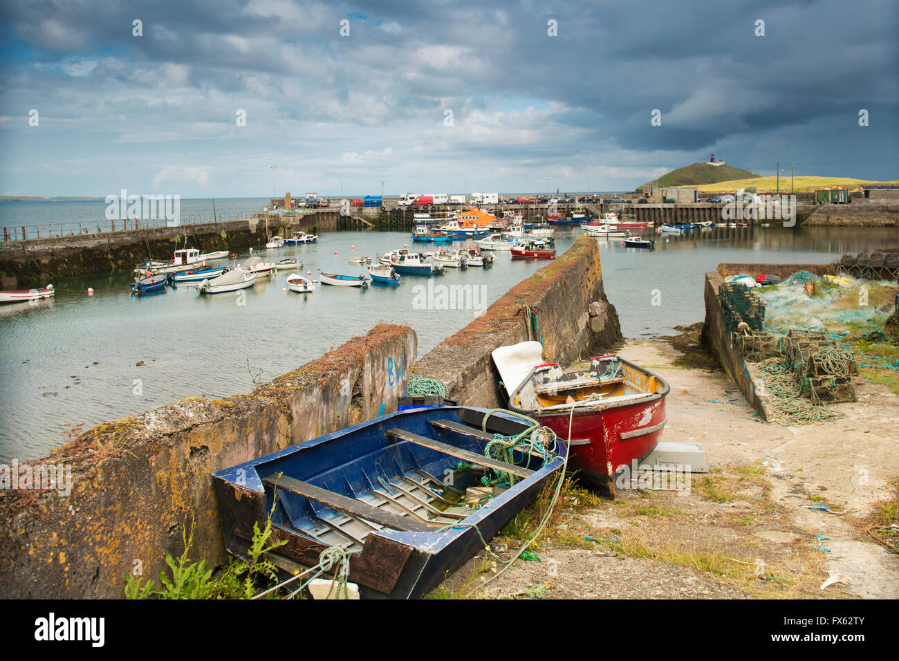 Old Colorful boats in the foreground with the boats in Ballycotton Harbour, Ballycotton Marina,County Cork, Ireland - Stock Image
