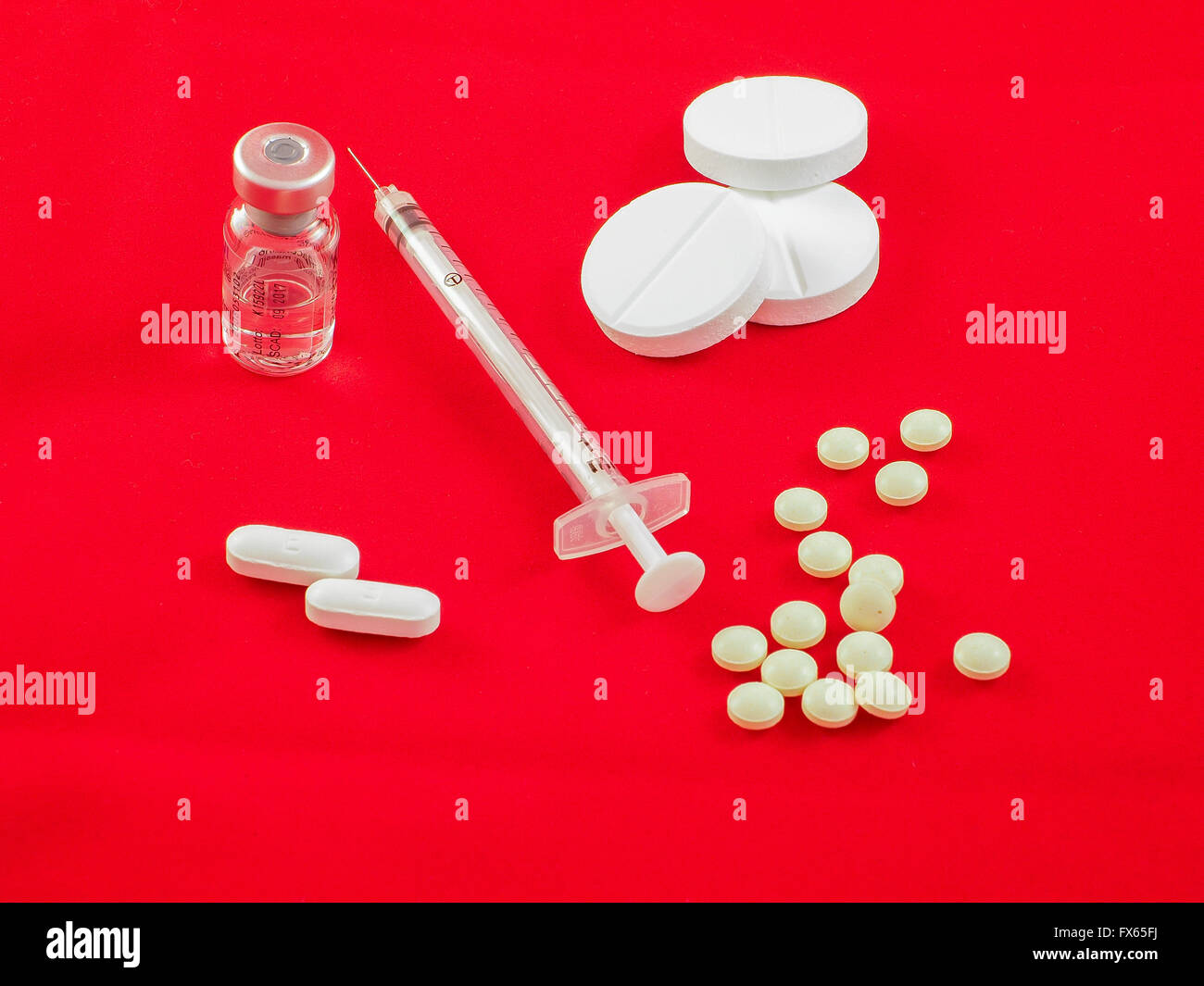 Several pills and caplets with different shapes, syringe and medecin bottle on red background. - Stock Image