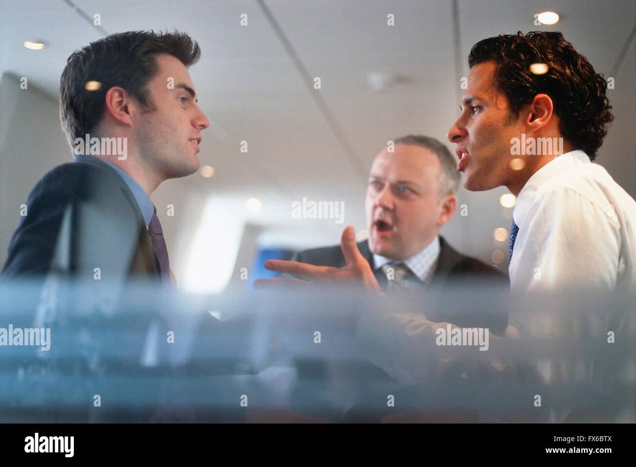 Caucasian businessmen arguing in office - Stock Image