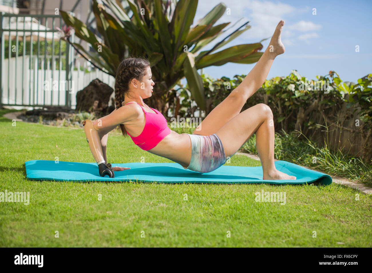 Mixed race amputee working out in grass Stock Photo