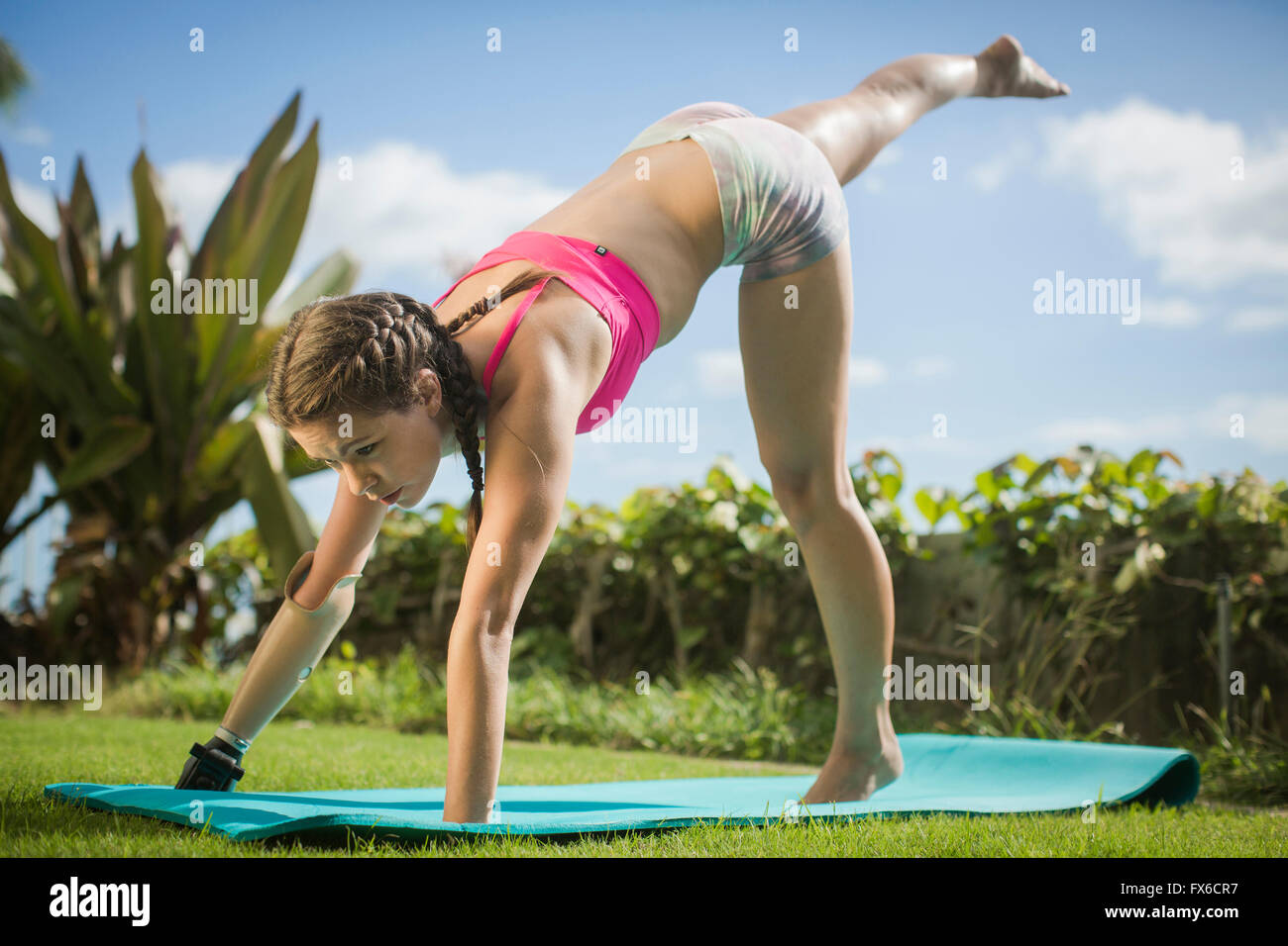 Mixed race amputee practicing yoga in grass Stock Photo