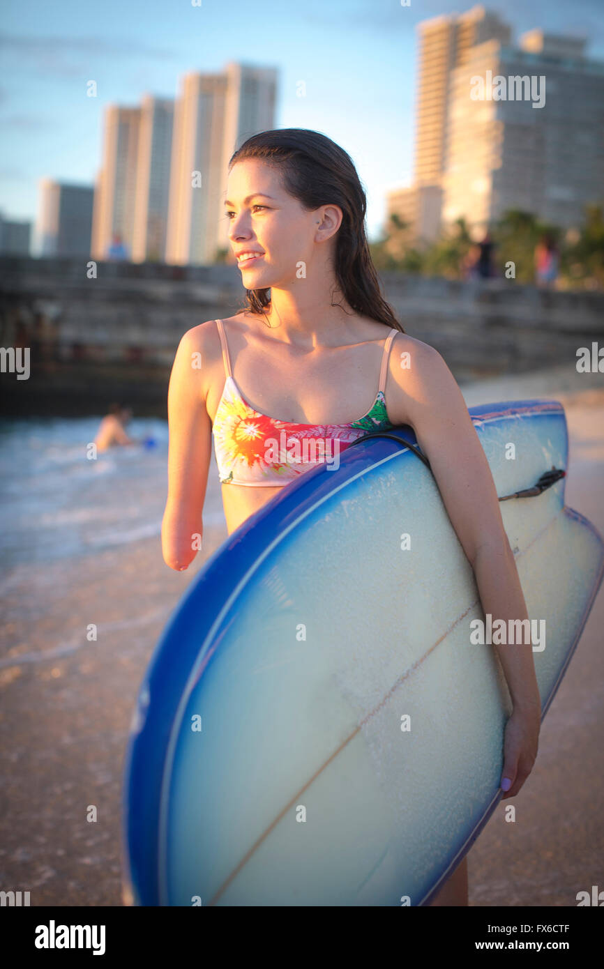 Mixed race amputee carrying surfboard on beach Stock Photo