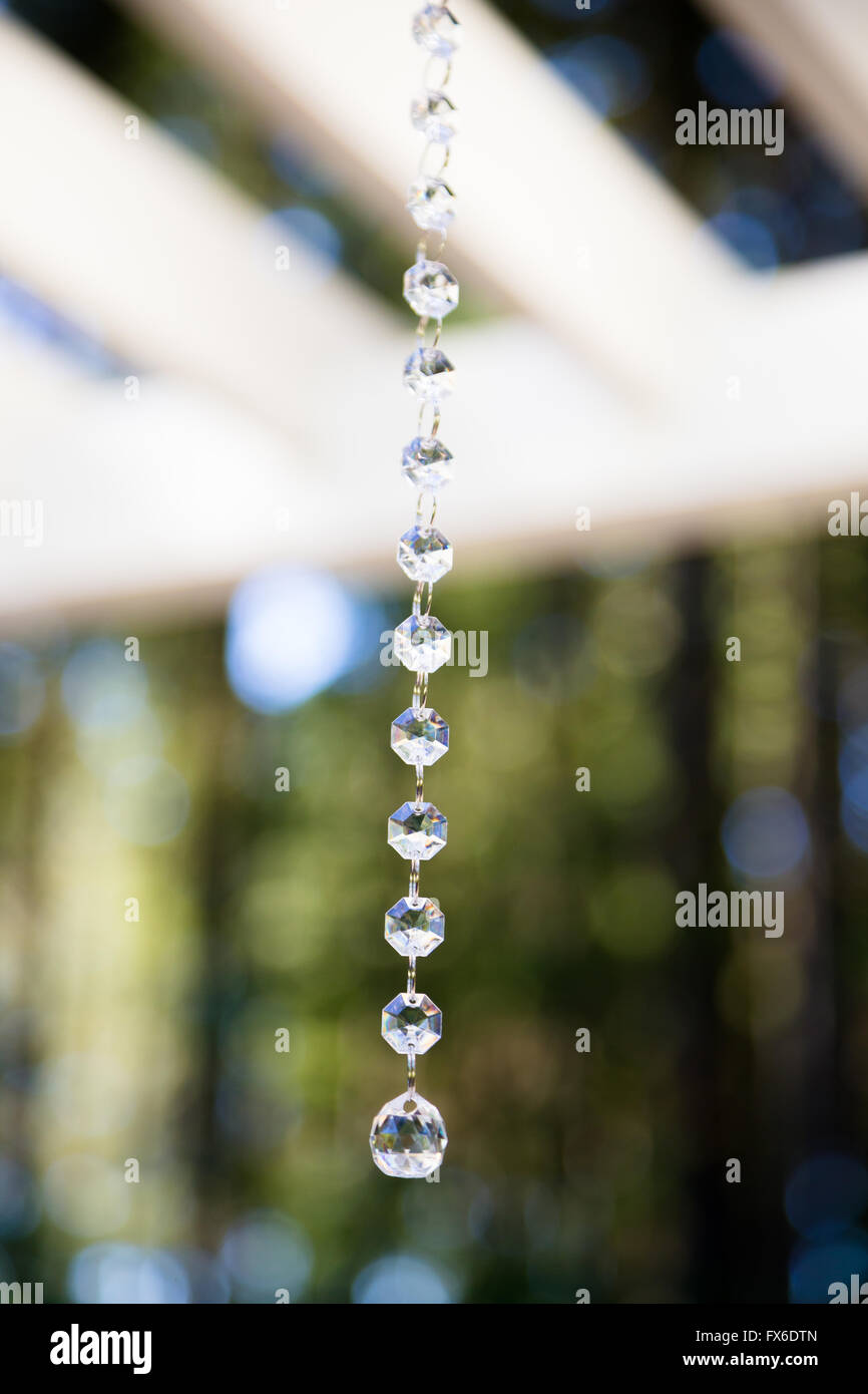 Wedding decorations hang from a pergola to be used in an outdoor ceremony. - Wedding Decorations Hang From A Pergola To Be Used In An Outdoor