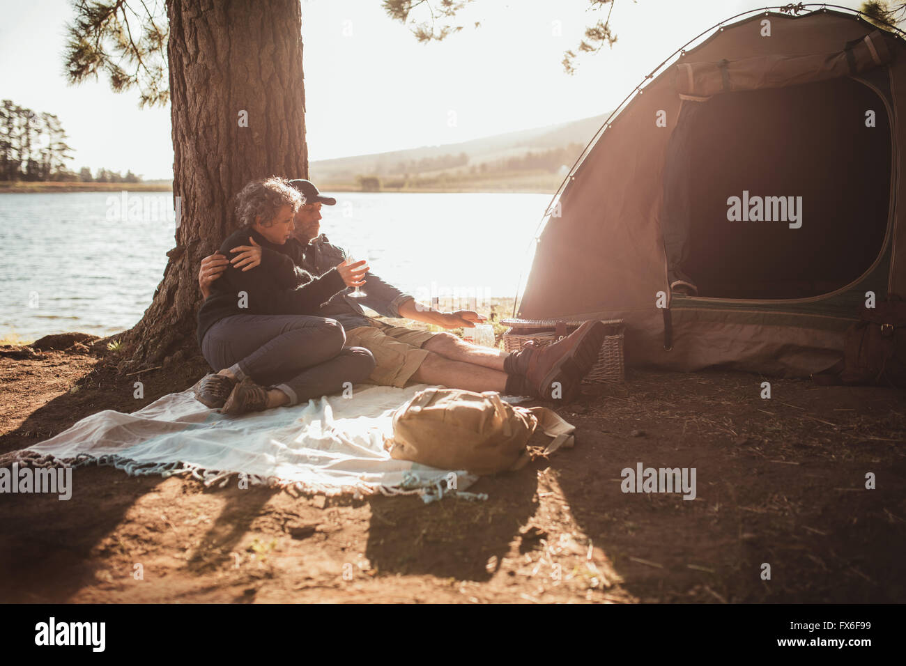 Portrait of loving senior couple camping near a lake on a beautiful summer day. They are sitting under a tree outside - Stock Image