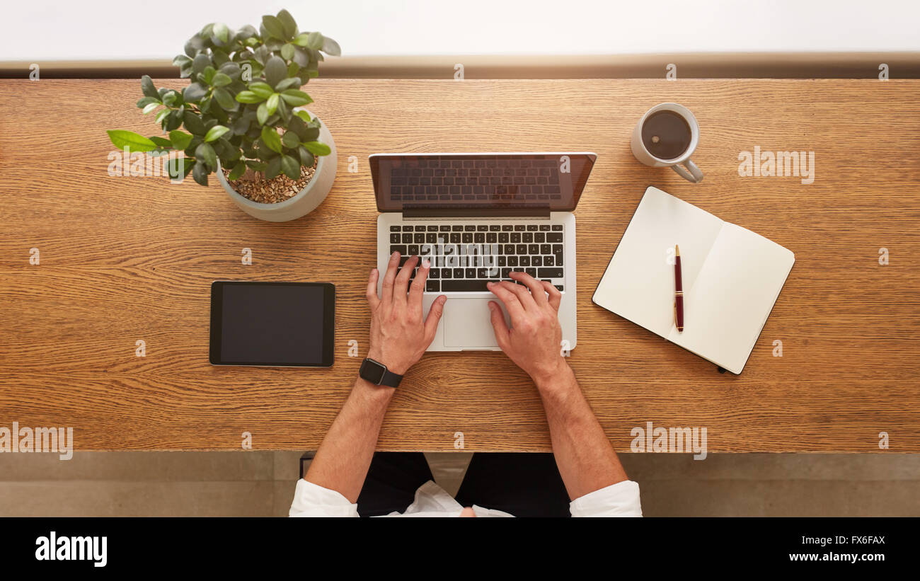 Directly above view of human hands typing on laptop. Laptop, digital tablet, diary, coffee cup and potted plant - Stock Image