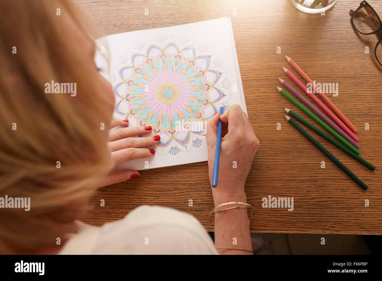 Overhead view of woman drawing in adult coloring book with color pencils. Anti stress exercise at home. - Stock Image