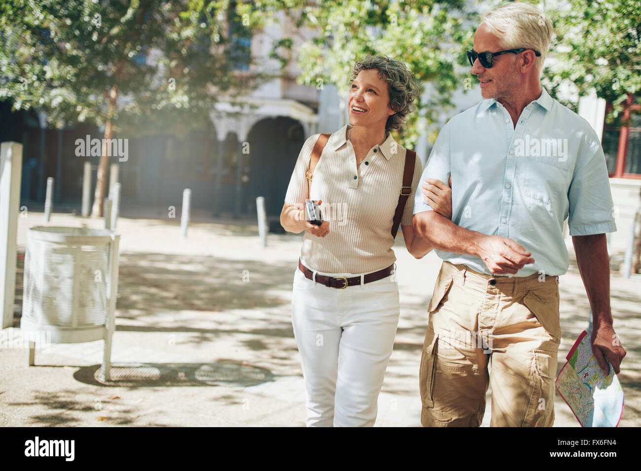 Senior couple on a vacation, roaming around in a foreign city. Man and woman walking in a town with camera and city - Stock Image