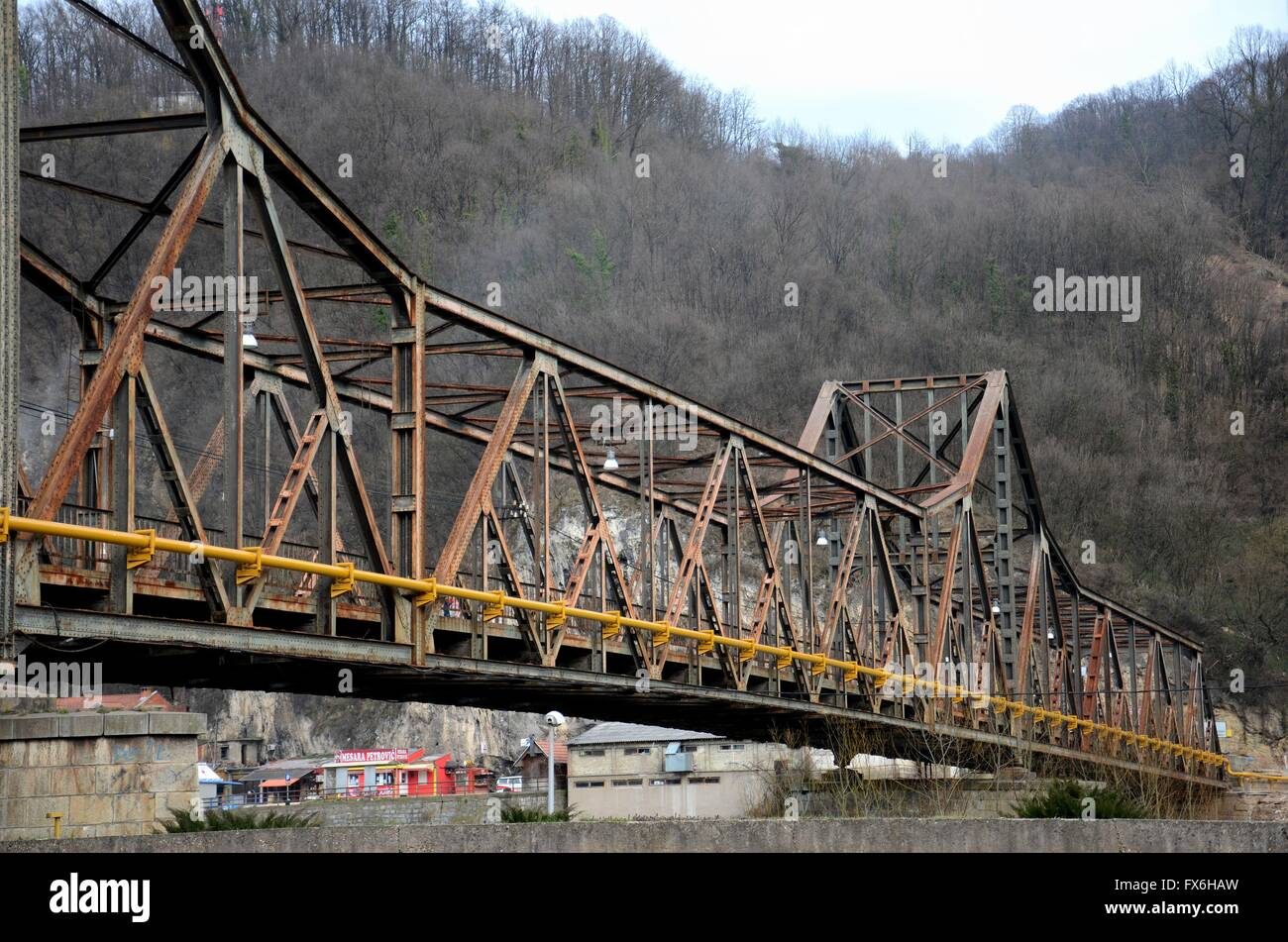Old Yugoslav rusty metal bridge across river with yellow pipe to town Bosnia Hercegovina - Stock Image