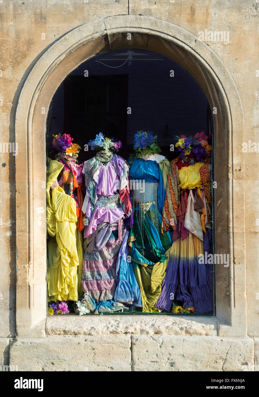 Colourful womens clothes in a shop window. Glastonbury, Somerset, England - Stock Image