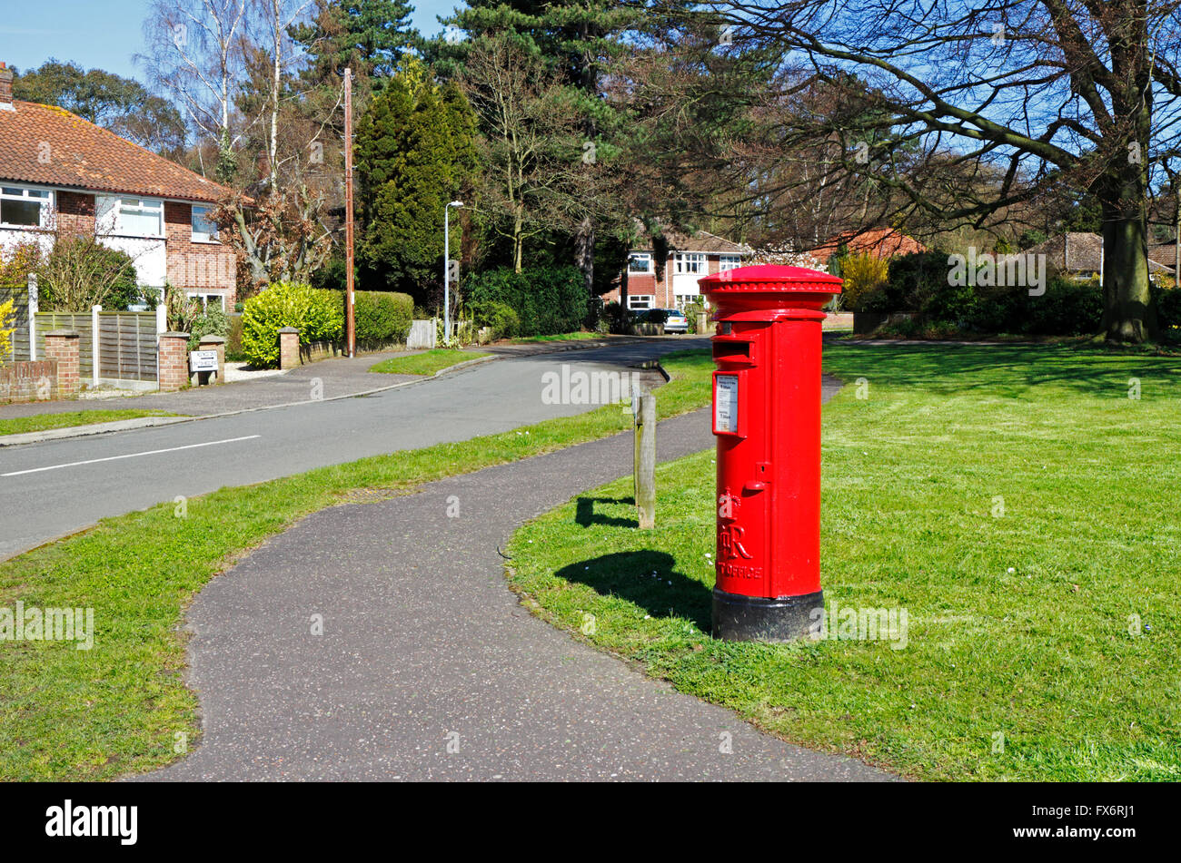 A view of a red post box on a street corner in Hellesdon, Norfolk, England, United Kingdom. - Stock Image