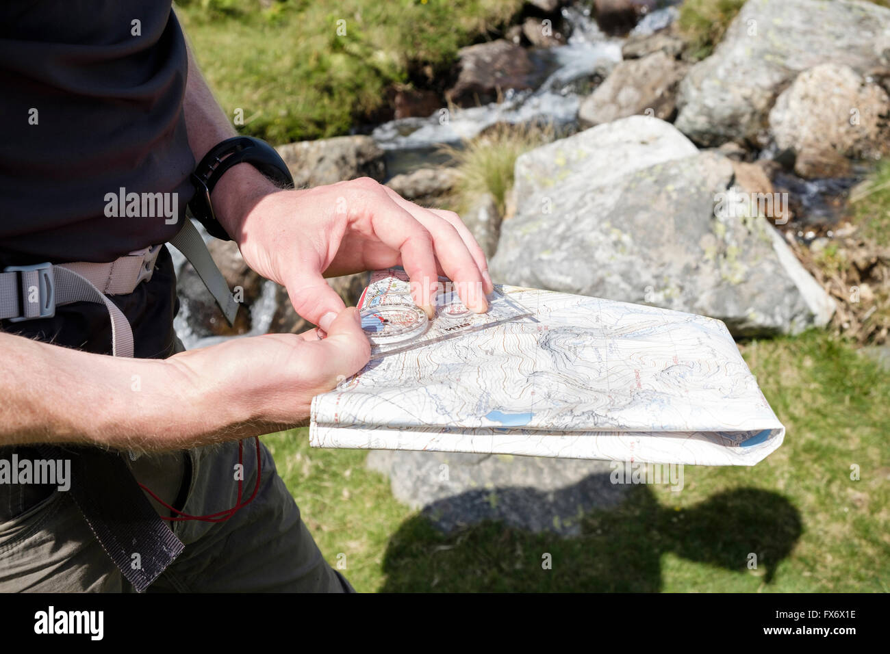 Hiker navigating the direction using holding a Harvey mountain map and Silva hiking compass to take a bearing in - Stock Image