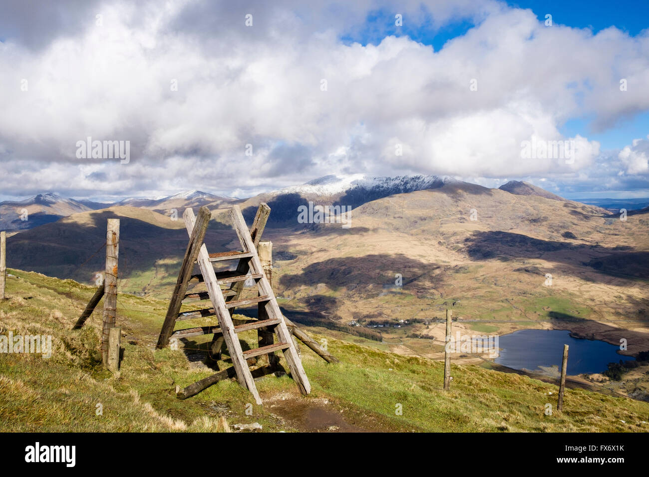 Ladder stile on path on Mynydd Drws-y-Coed on Nantlle Ridge with snowcapped Mount Snowdon in clouds in Snowdonia Stock Photo