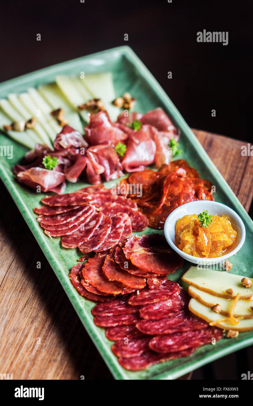 spanish traditional smoked meats serrano ham chorizo and cheese platter starter dish with quince jam and bread - Stock Image
