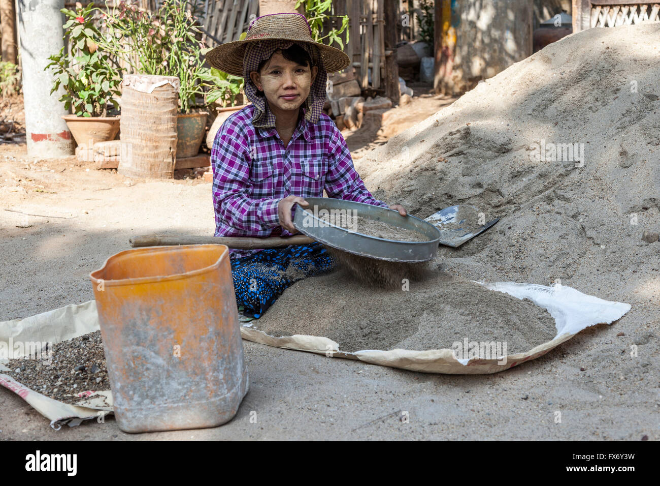 At New Bagan, an apprentice young woman preparing the mortar for workmen on a construction site (Myanmar). - Stock Image