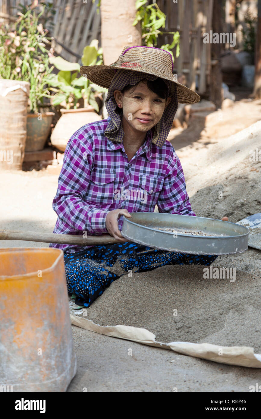 At New Bagan, an apprentice young woman preparing the mortar for workmen on a construction site (Myanmar) Stock Photo