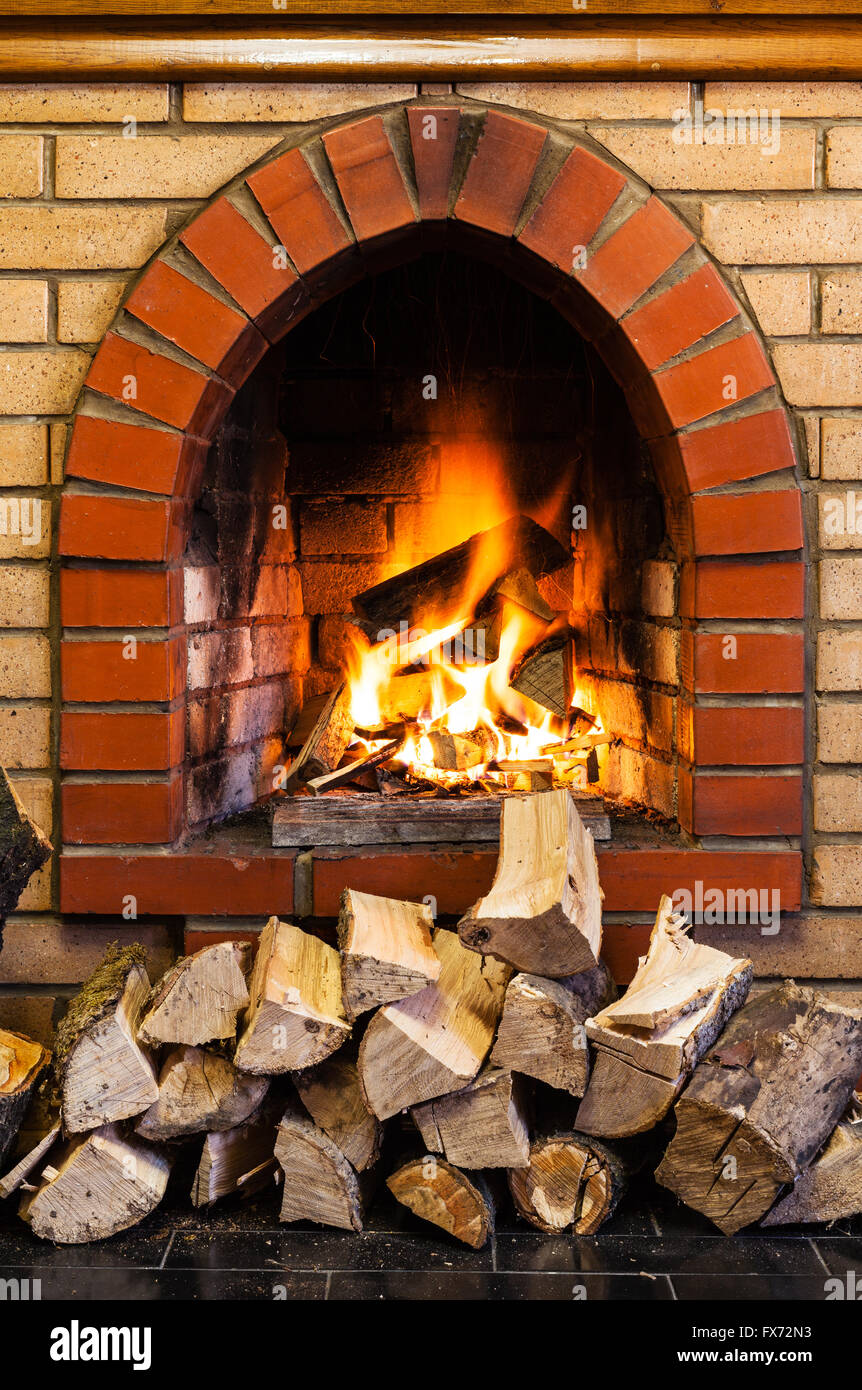 Stack Of Wood And Fire In Indoor Brick Fireplace In Country Cottage