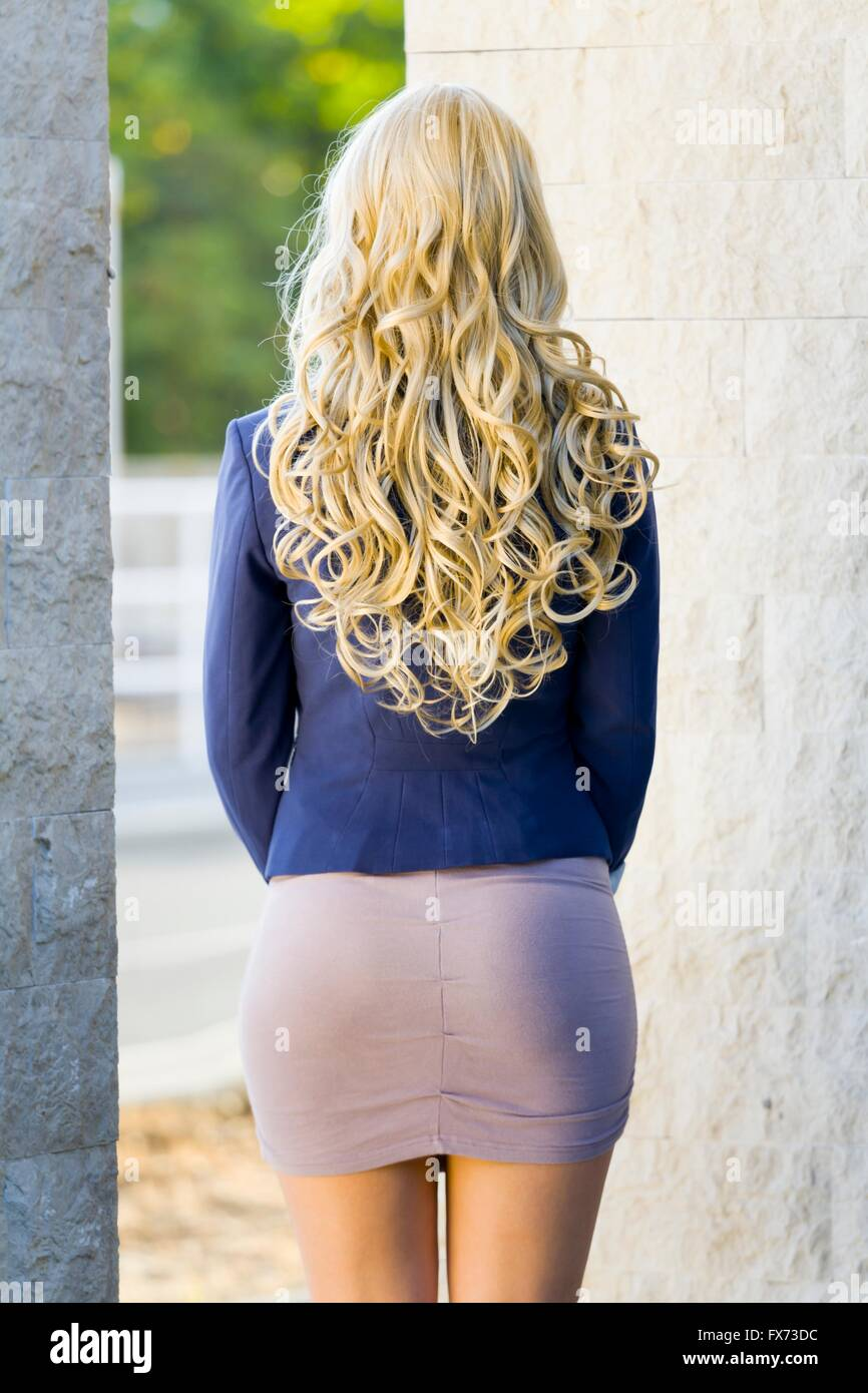 Curly hair young woman blonde rearview Blue suit mini short dress minidress curls hairdo beautiful attractive rear Stock Photo