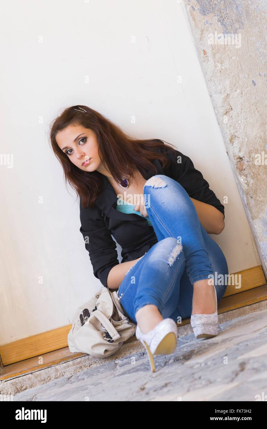 13d75551c244 Tired teen-girl outdoors sitting low by wall looking at camera eyes-contact  serious denim pants Black stilettos stiletto pumps shoes