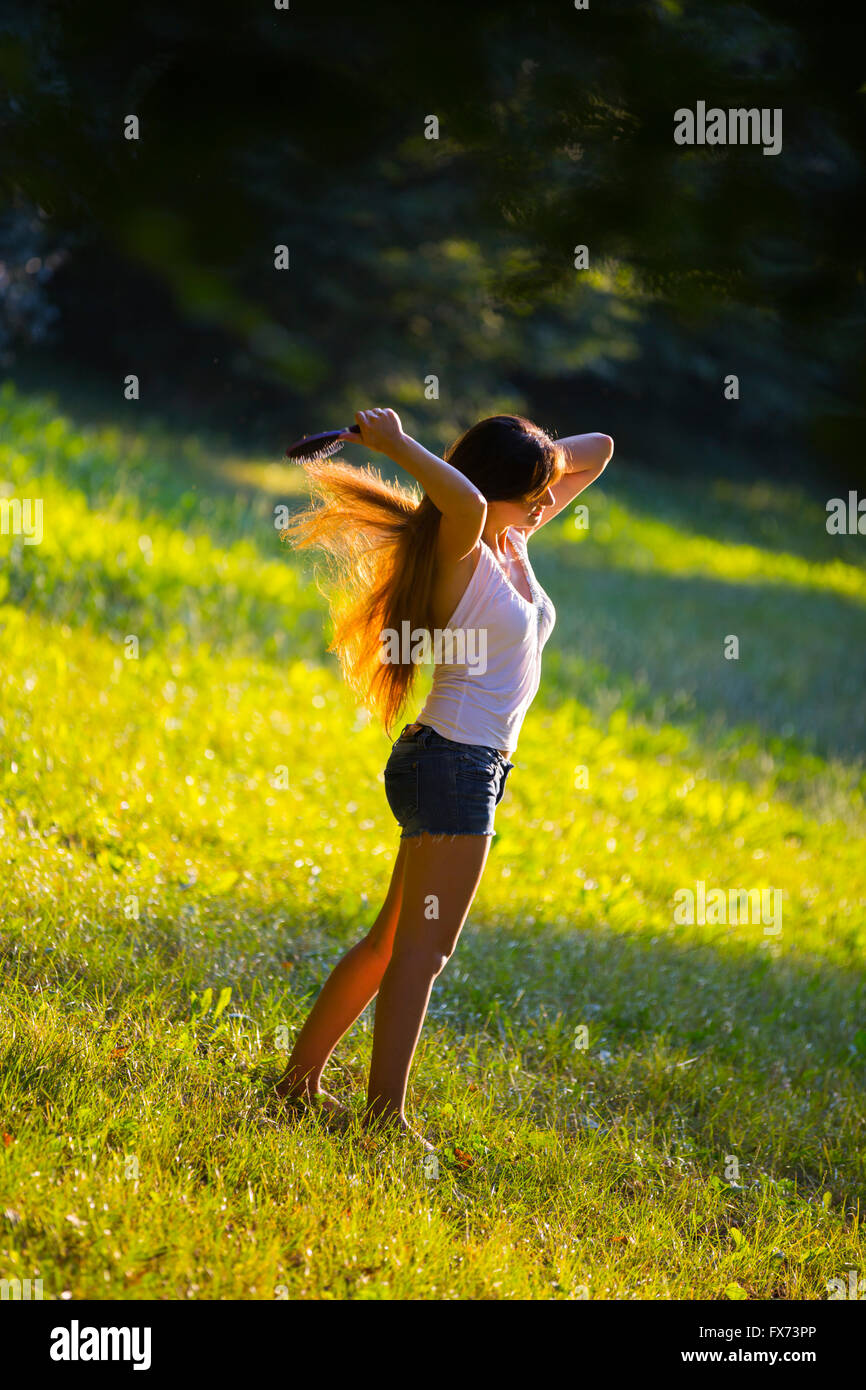Brushing her golden hair in nature walking walk in nature ordinary people single hotpants shorts Stock Photo