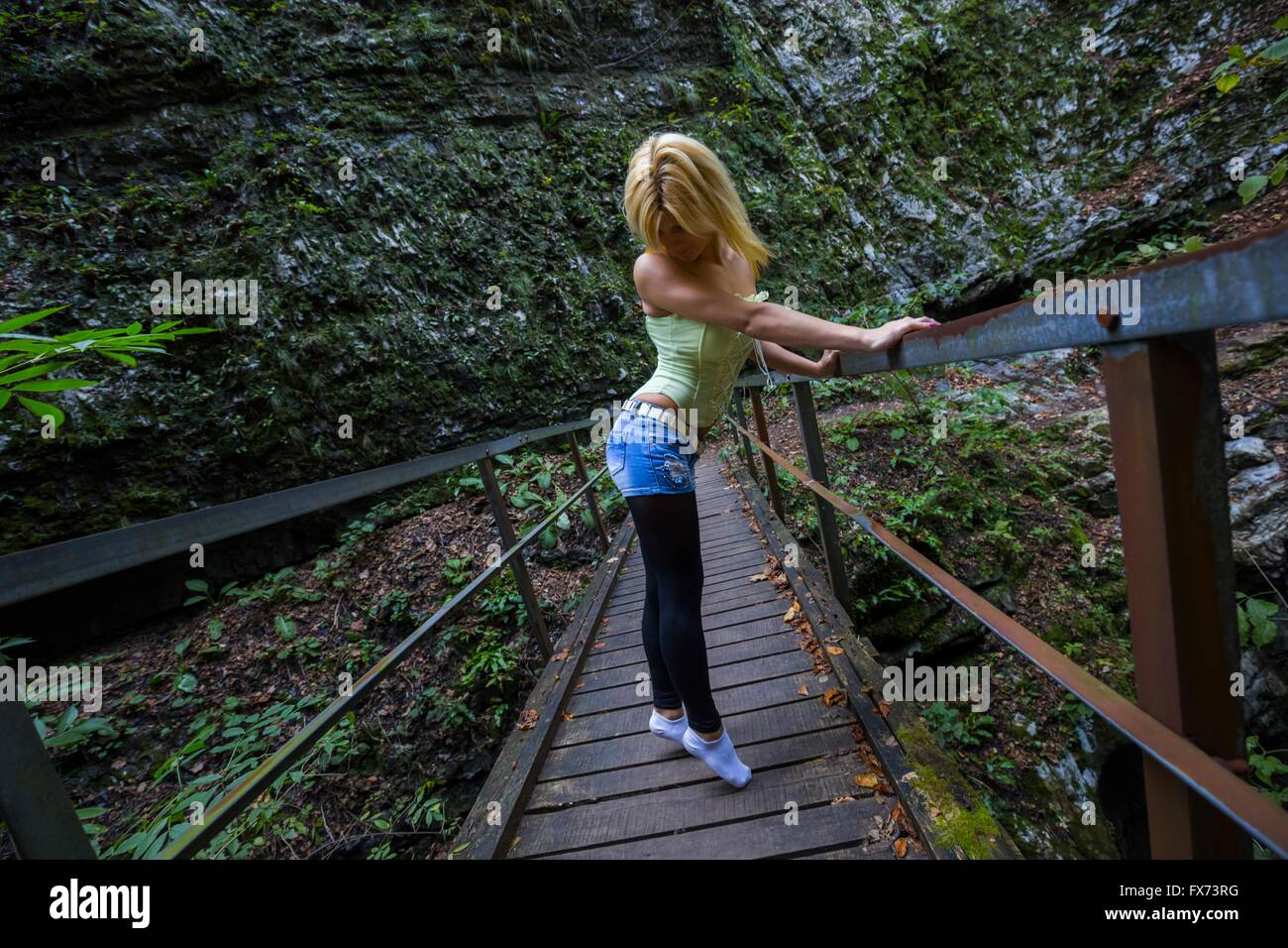 Tip-toeing pretty woman on small bridge in forest beautiful attractive single stand standing - Stock Image