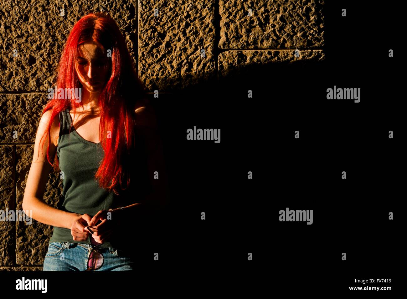Red-haired woman with glasses in hands sunset sidelit sidelight Stock Photo