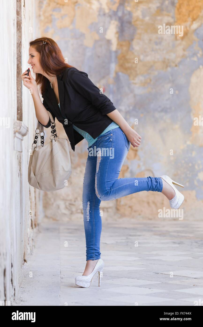 Fixing adjusting makeup denim pants balance balancing one leg heels handbag Black jacket outdoors stiletto stilettos Stock Photo