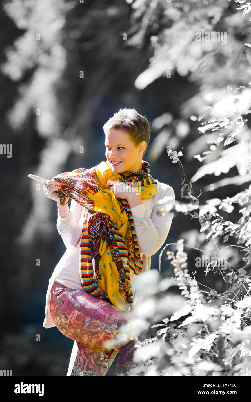 Short-haired teenager girl in woodland pointing with finger smiling happy attractive beautiful single scarf standing - Stock Image