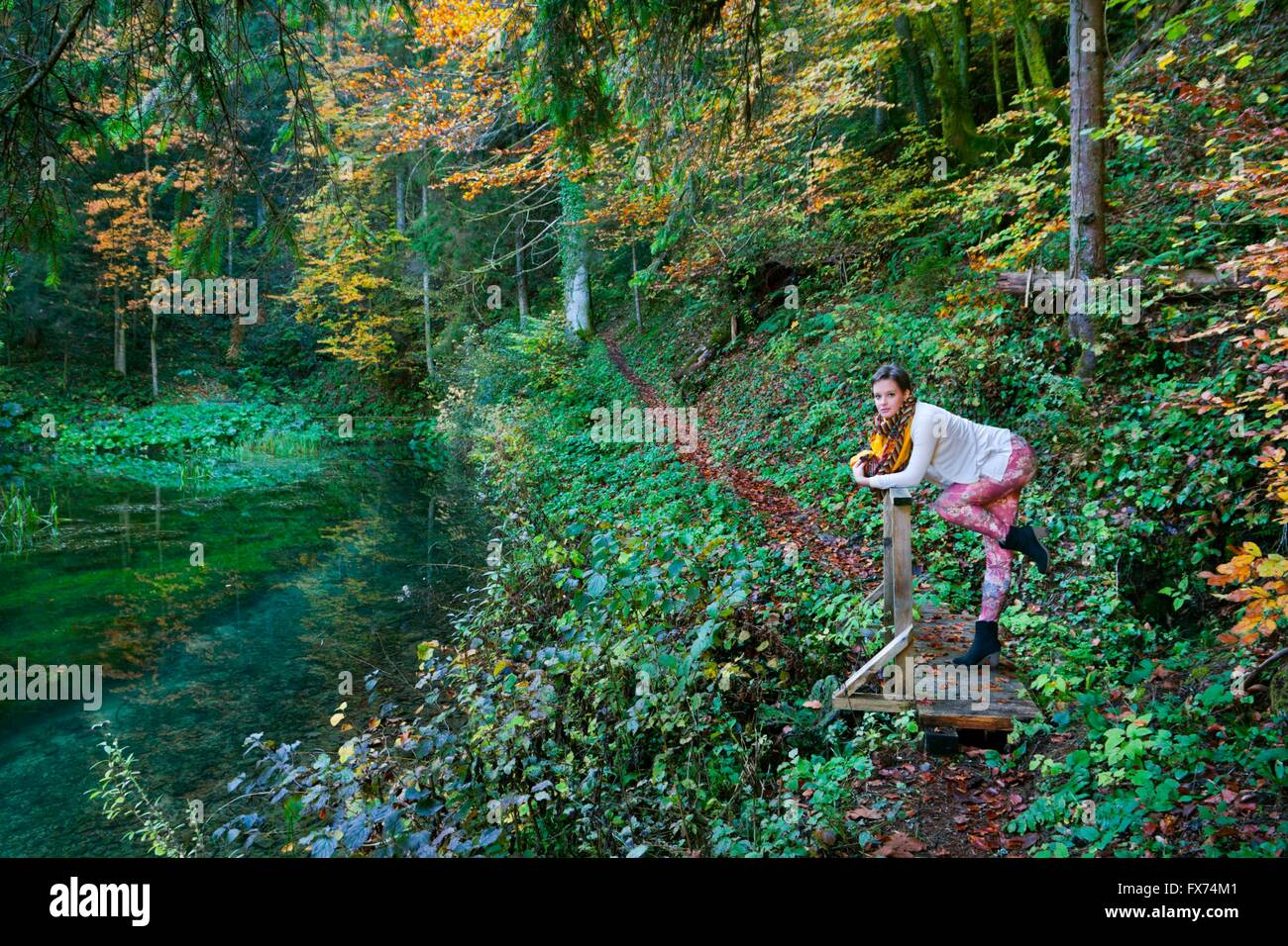 Short-haired teenager girl in woodland forest posing pose colorful pants Autumn Fall trail lake deep trees strike pose striking Stock Photo