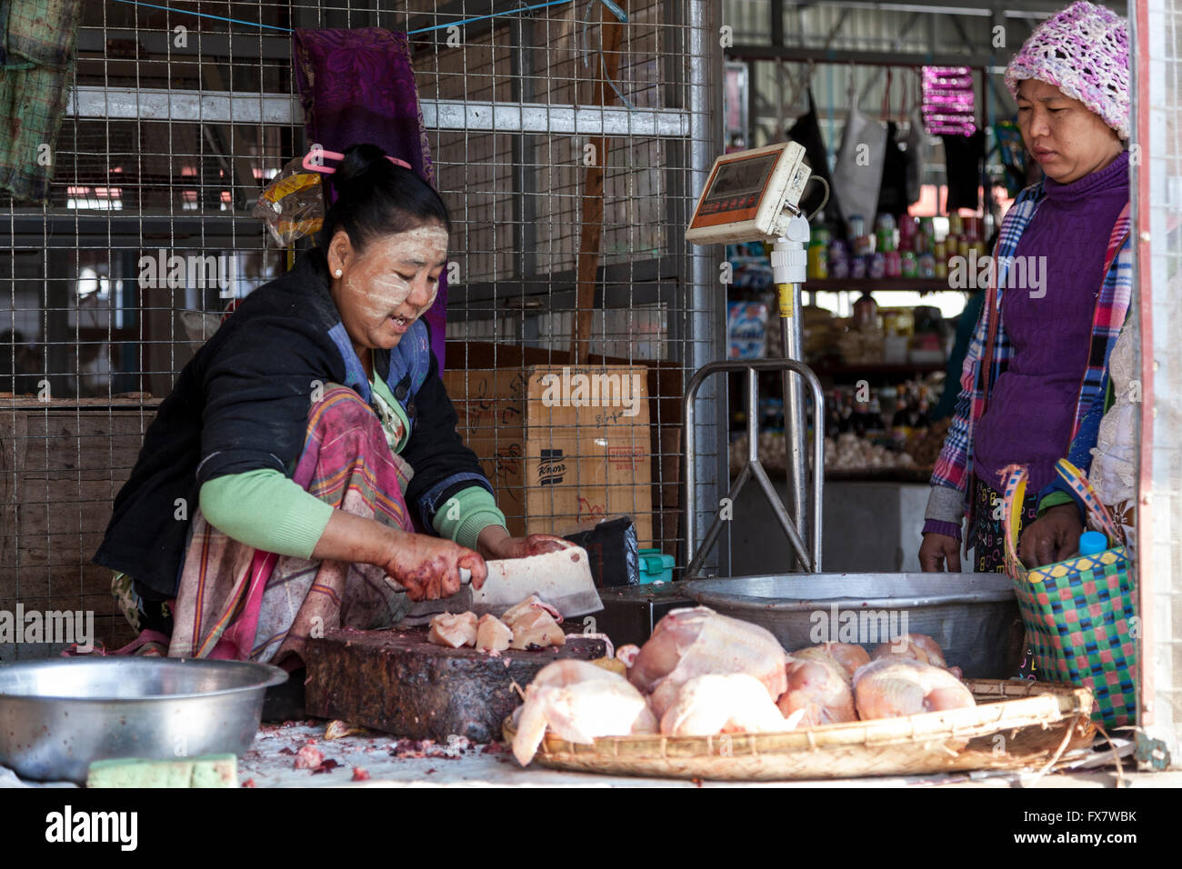 A woman butcher carving the fresh meat on the bare ground, at the New Bagan market (Myanmar). - Stock Image