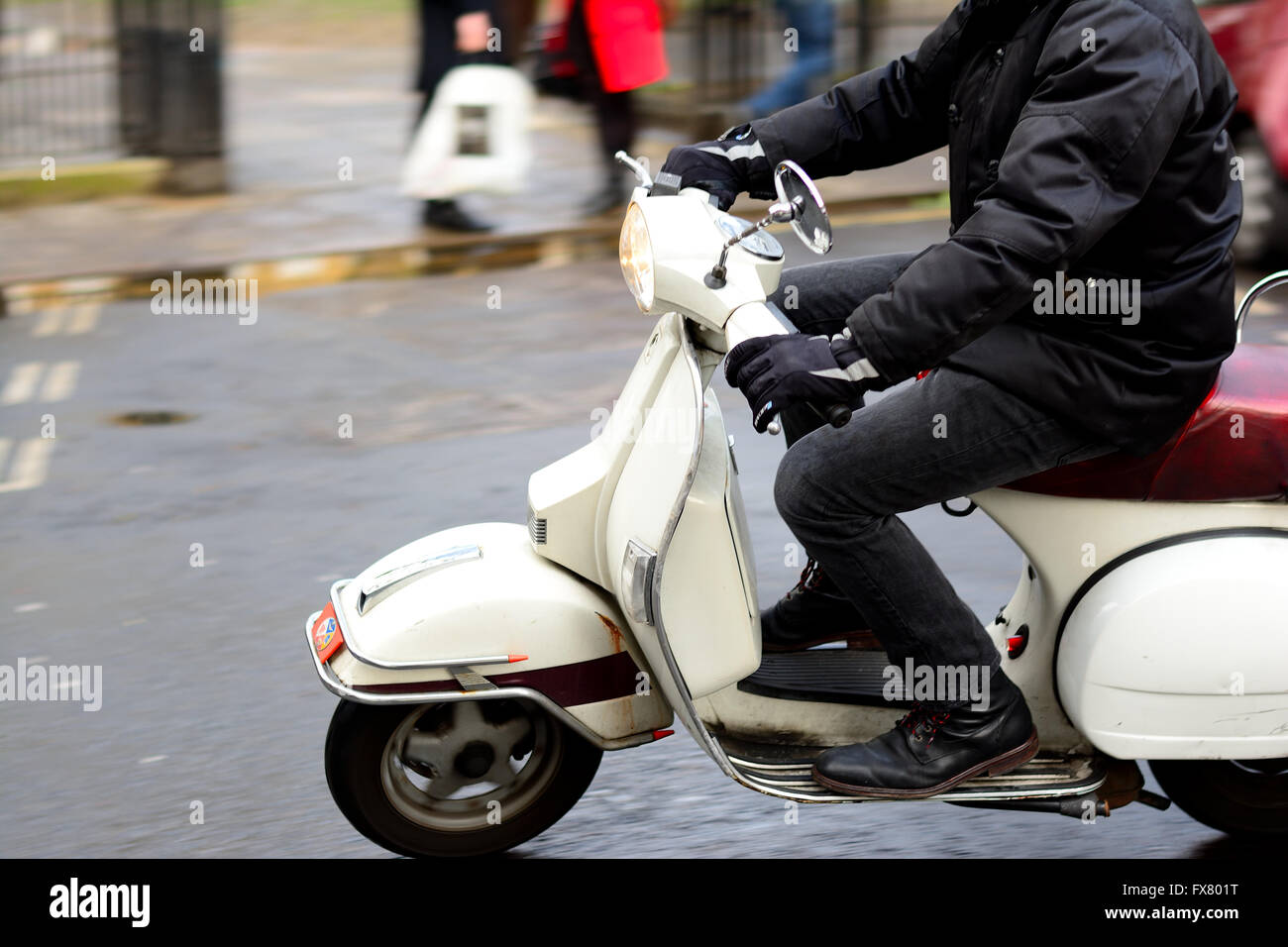 White Vespa scooter ridden by man during wet weather in London - Stock Image