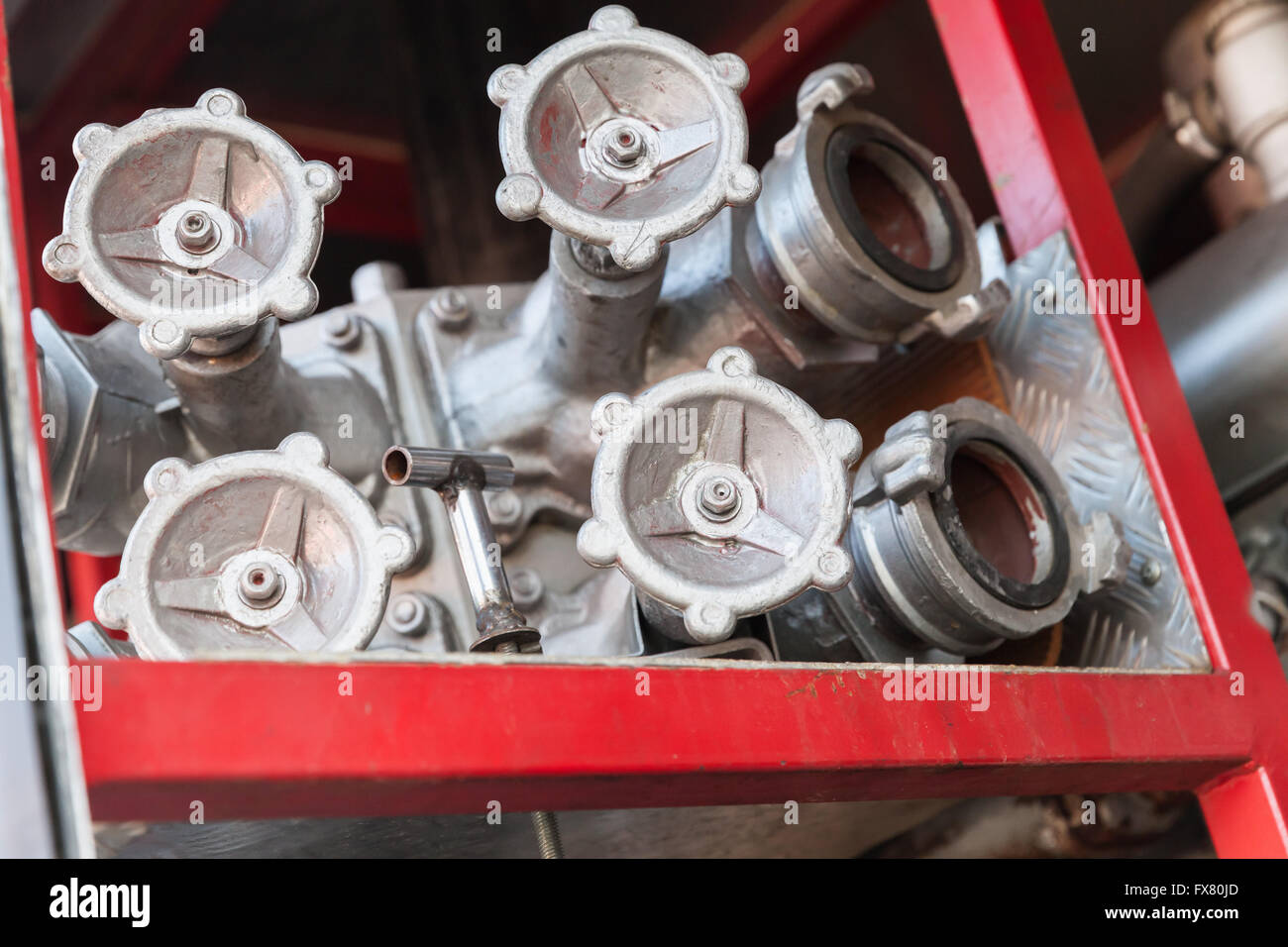 Firefighting equipment on red fire truck. Water hydrants closeup photo with selective focus - Stock Image