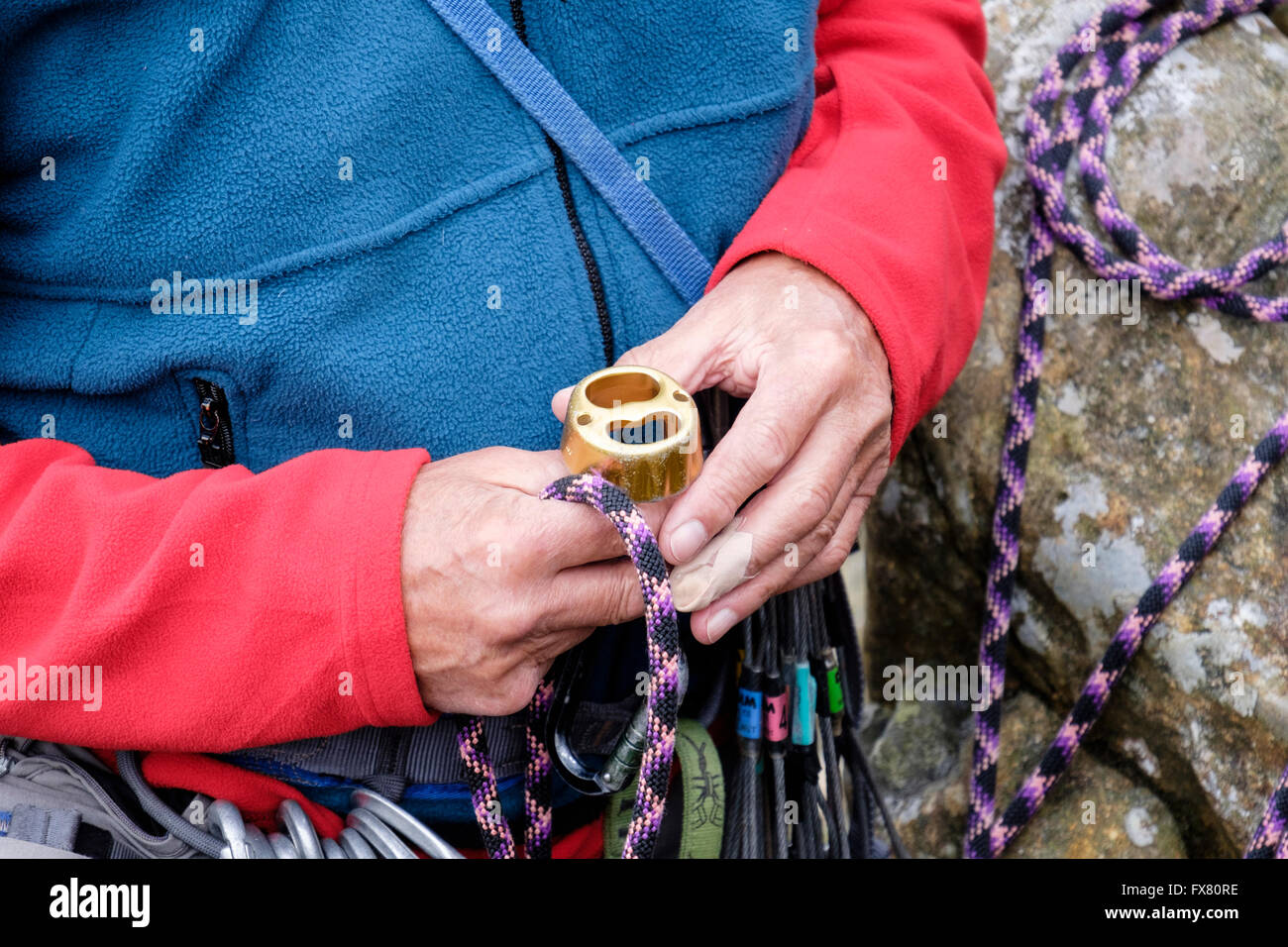 Mountain climber holding a belay device rappel descender for abseiling or belaying. Wales, UK, Britain - Stock Image