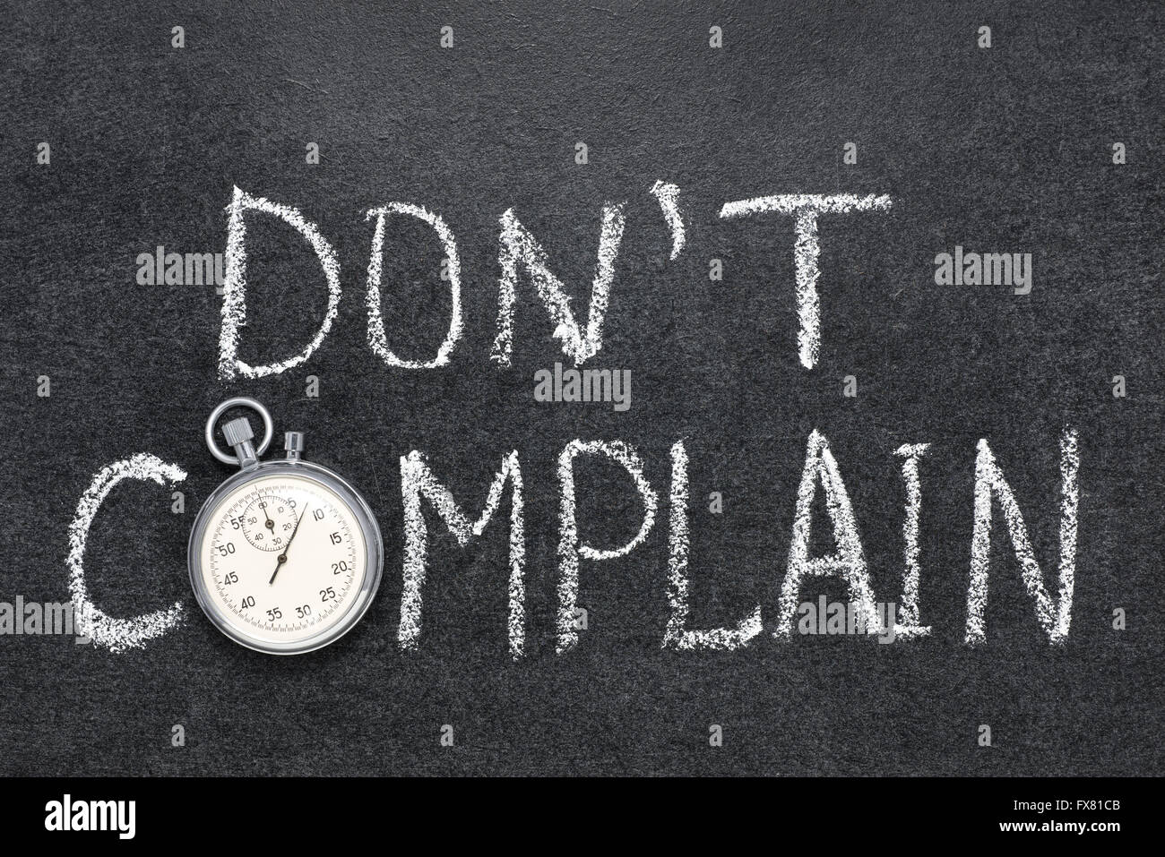 dont complain phrase handwritten on chalkboard with vintage precise stopwatch used instead of O - Stock Image