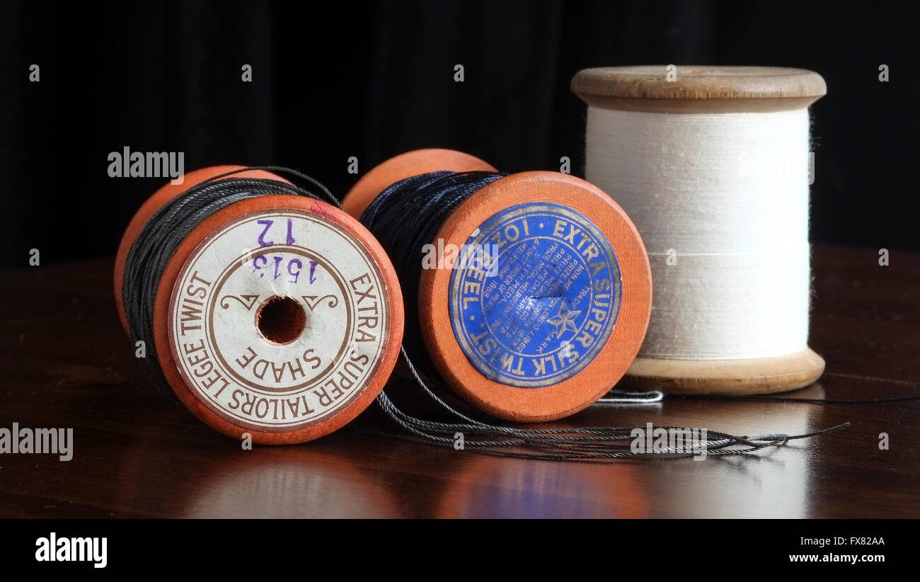 Three vintage taylor's cotton bobbin reels with blue, grey and white thread - Stock Image