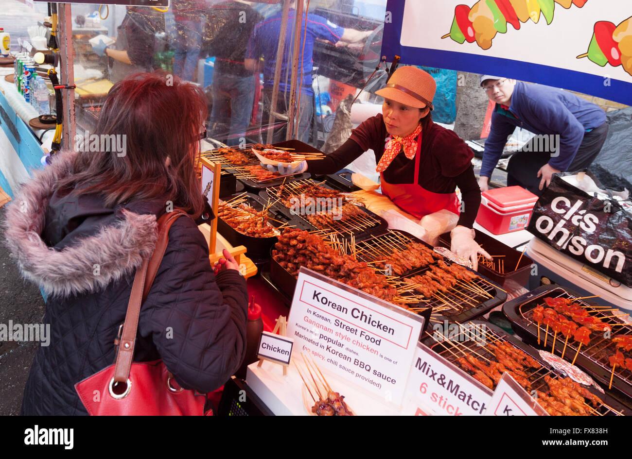 People buying food, Brick Lane Sunday Upmarket, Brick Lane, Spitalfields, East End, London UK - Stock Image