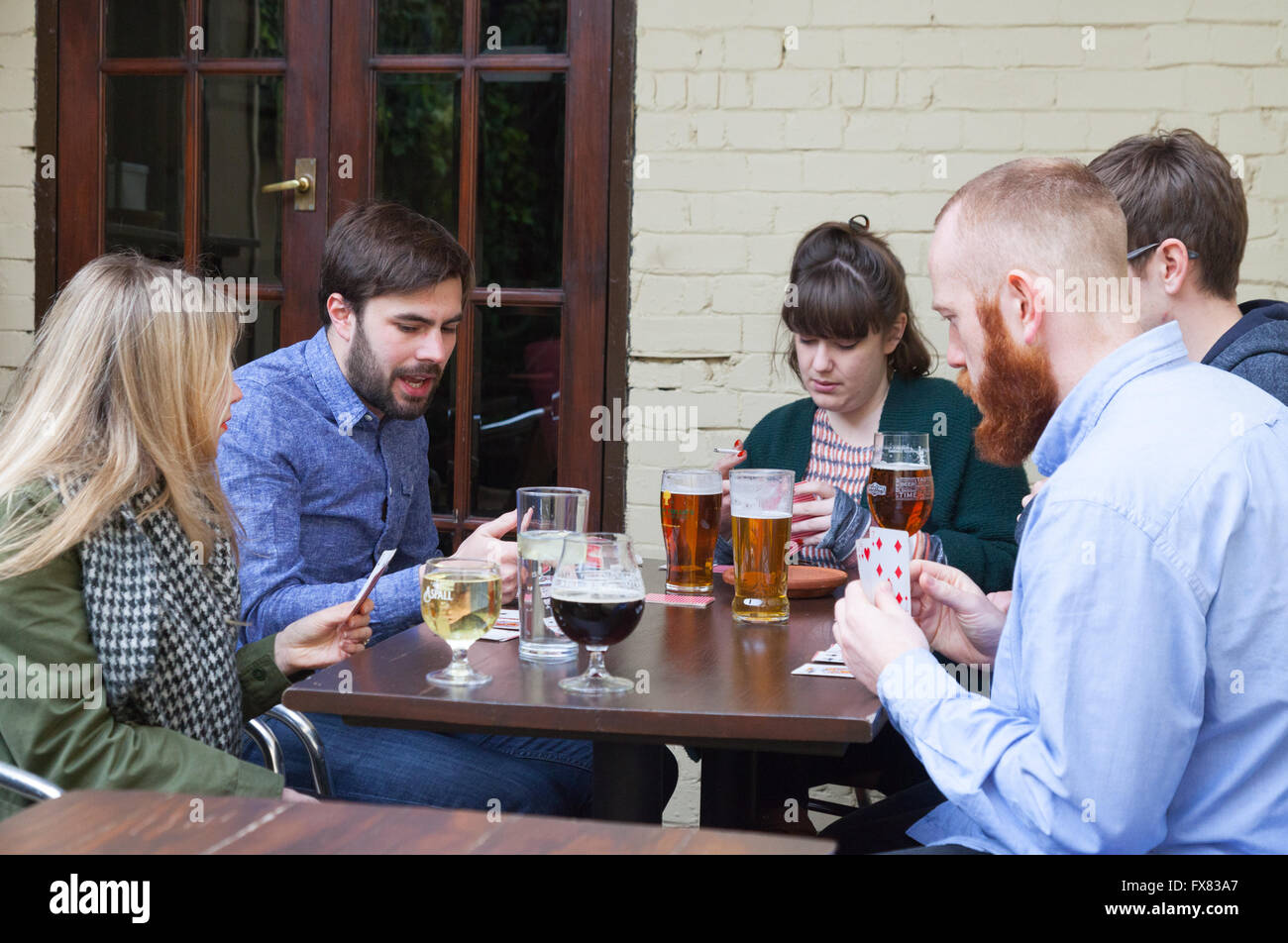 People drinking beer and playing cards in a london pub, The Carpenters Arms, Cheshire Street, Spitalfields, East - Stock Image