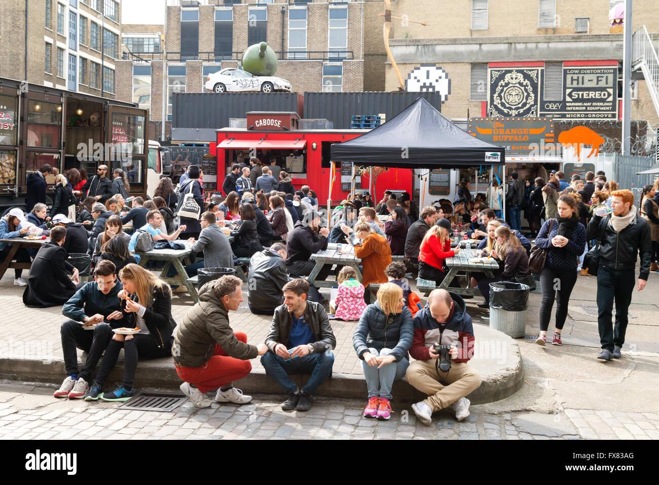 People sitting in the street, Brick Lane Sunday Upmarket, Spitalfields, London East End, UK - Stock Image