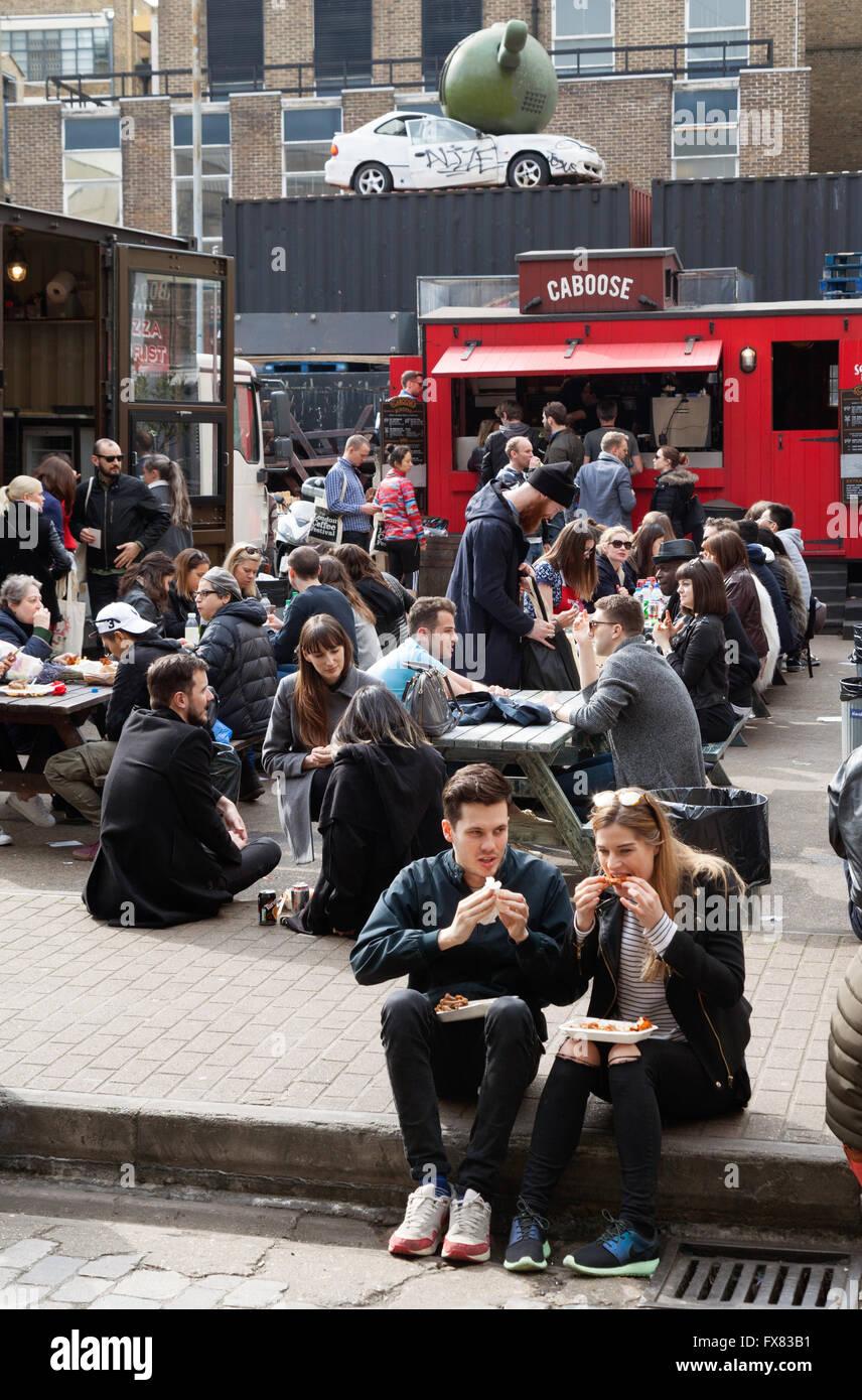 People eating at the Sunday Upmarket, Brick Lane, Spitalfields, London east End UK - Stock Image