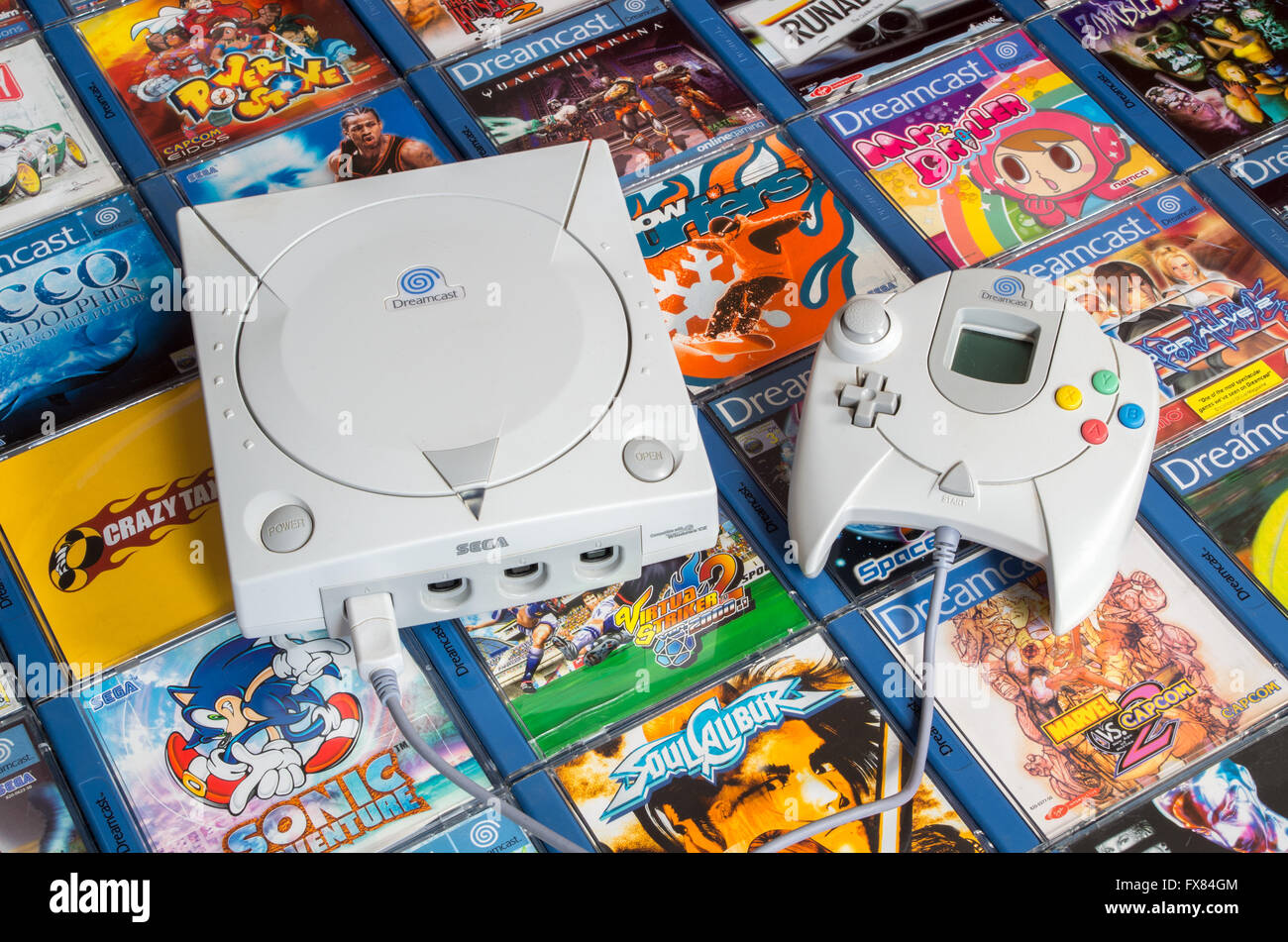 A European Sega Dreamcast console and hand controller are shown on a bed of PAL region games including Sonic Adventure. - Stock Image