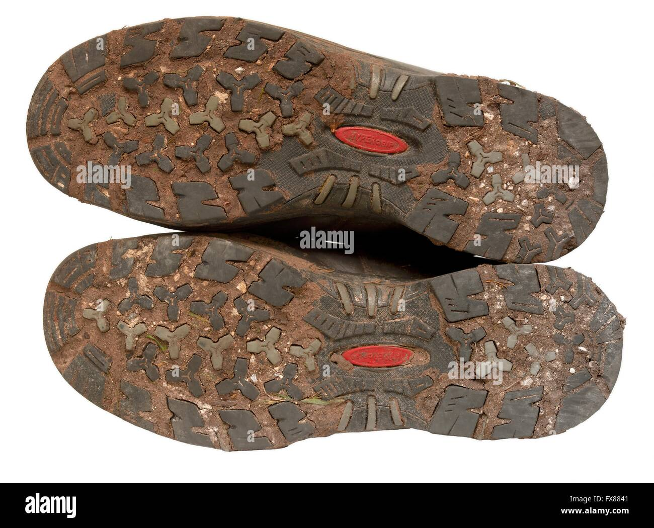 Dried mud on the underside of a pair of walking boots - Stock Image