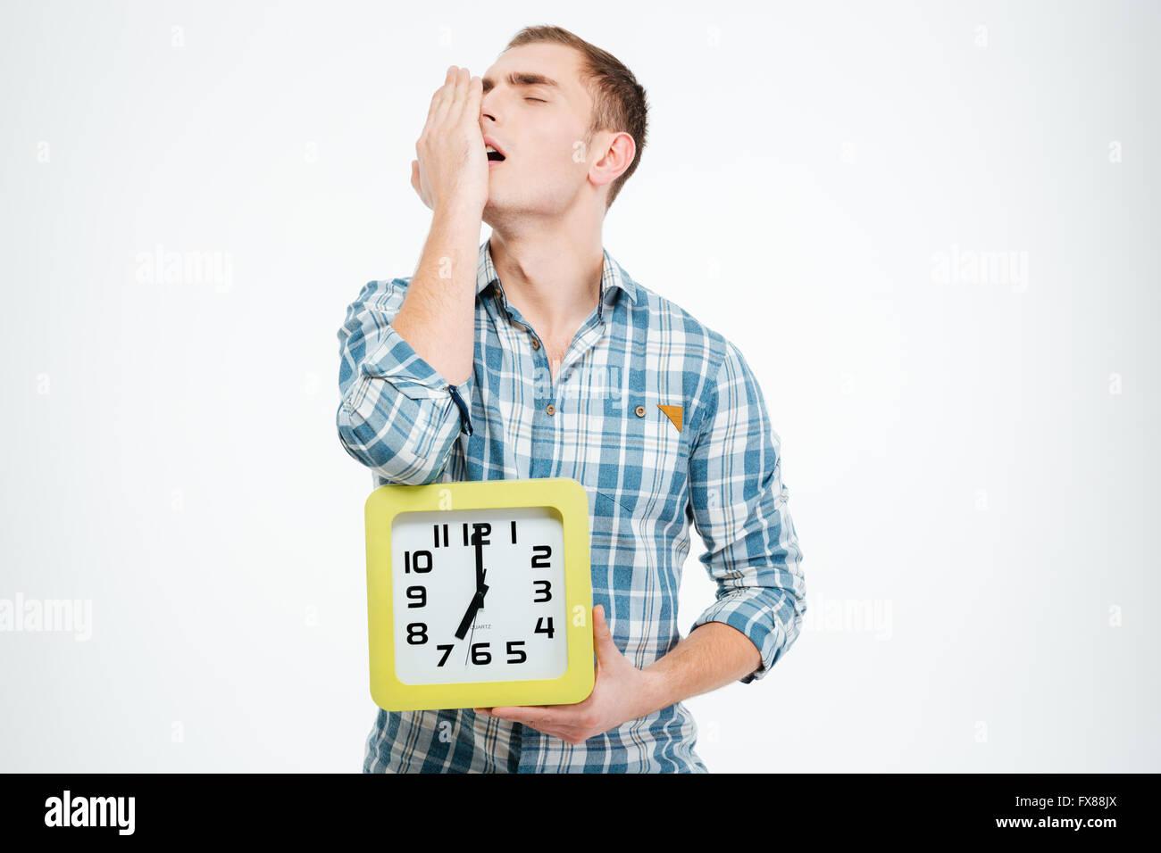 Sleepy tired man yawning and holding clock over white background - Stock Image