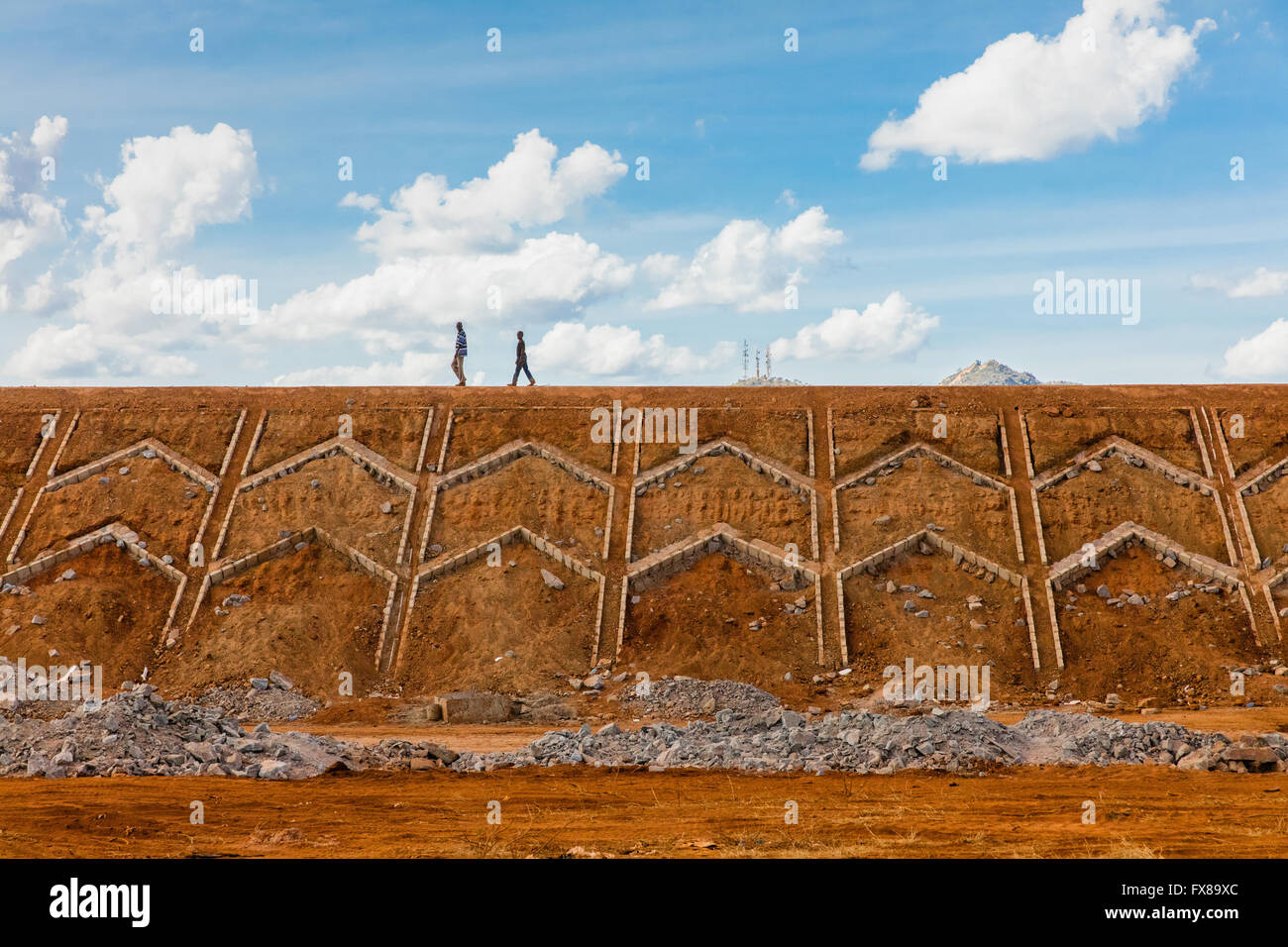 Two men walking along a newly built earth embankment of the Nairobi to Mombasa section of the China funded SG Railway - Stock Image
