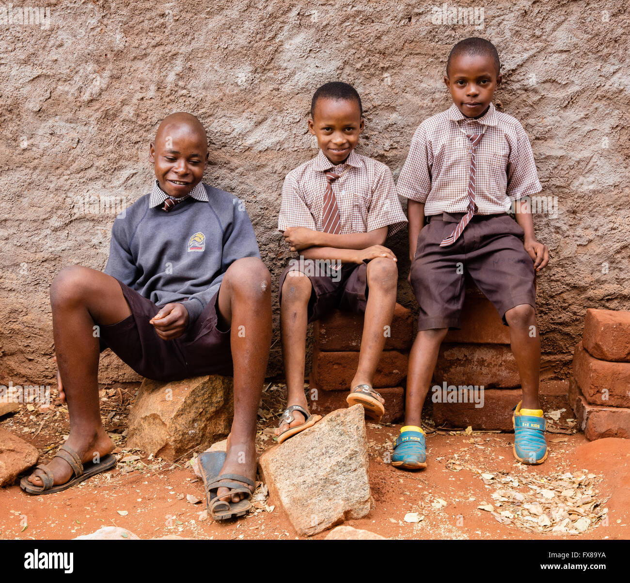 Three schoolboys of varying heights take a break at a primary school near Voi in Southern Kenya - Stock Image