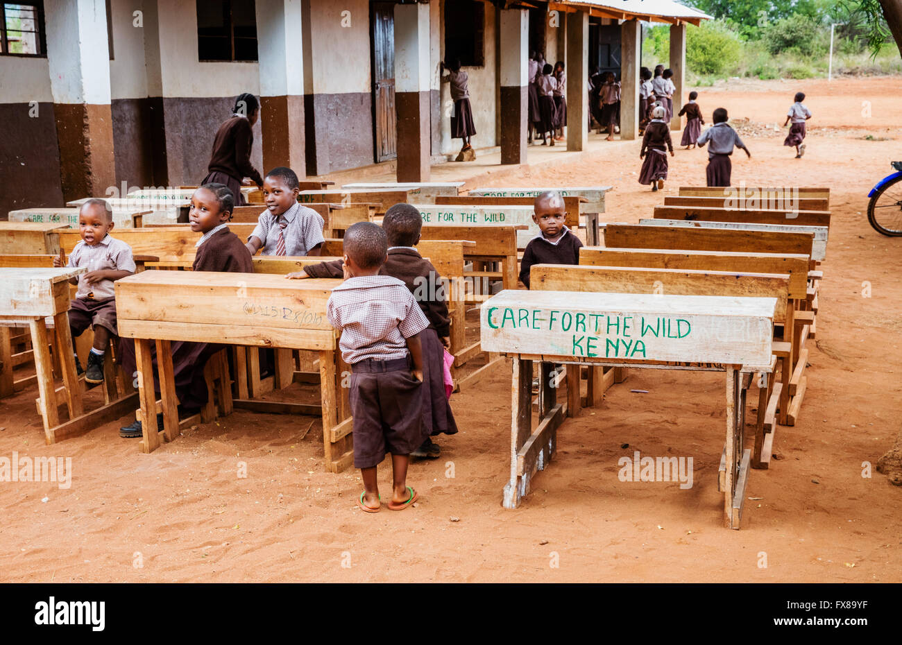 Children at charity desks set outdoors in a primary school near Voi in Southern Kenya - Stock Image